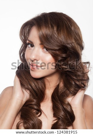 beautiful female face with make-up and shiny curly hair. Elegant hairstyle for long hair - stock photo
