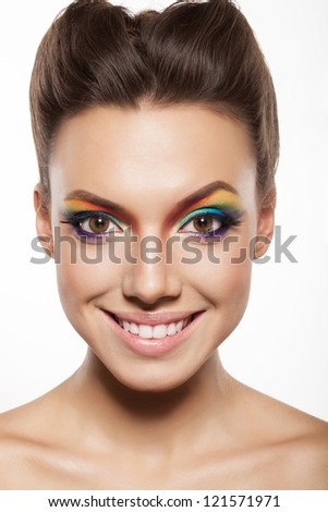 beautiful female face with rainbow makeup. girl showing joy and smiling - stock photo