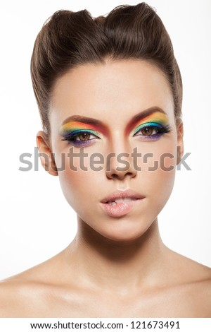 beautiful female face with rainbow makeup. intriguing girl biting her lip - stock photo