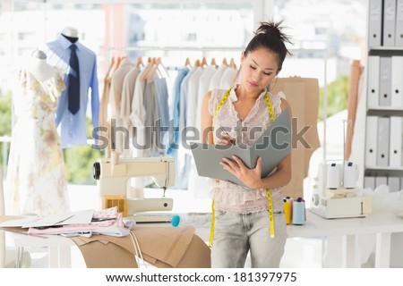 Beautiful female fashion designer looking at folder in the studio - stock photo