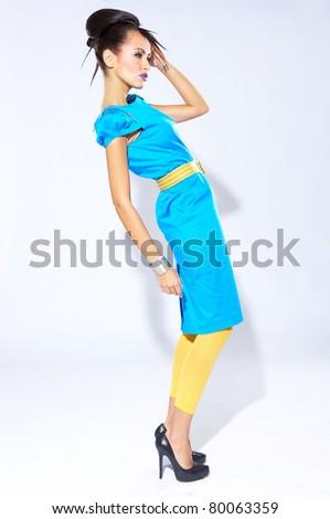 Beautiful female fashion model in blue dress on white - stock photo