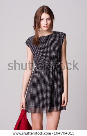 Beautiful female fashion model in polka dot dress isolated over - stock photo