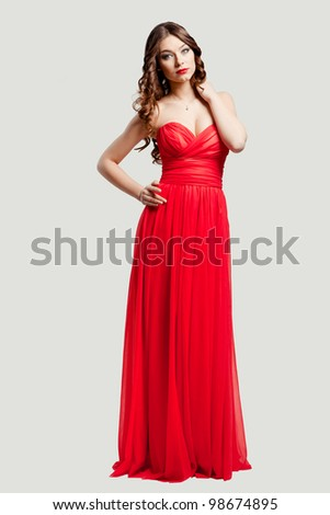 Beautiful female fashion model posing in red dress - stock photo
