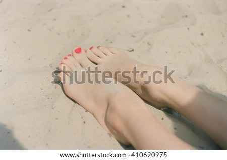 Beautiful female feet in the sand. The most beautiful legs of the young girl, soft white skin. The beach, golden sand, shade, rest. Lovely fingers. Art photo. Unusual colors. Real analog photo film - stock photo