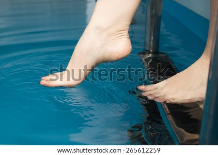 Beautiful female feet on the steps of the pool. - stock photo