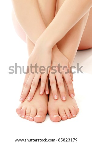 Beautiful female feet with  crossed hands on them isolated on white background