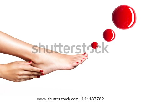 Beautiful female feet with red pedicure and drops of nail polish  over white background - stock photo