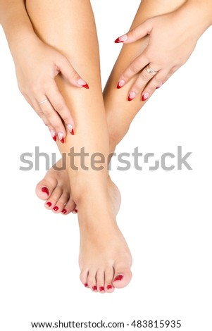 Beautiful female feet with red pedicure and hand with red manicure, isolated