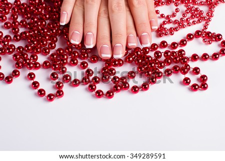 Beautiful female fingernails on a background of red beads. Gentle french manicure. - stock photo