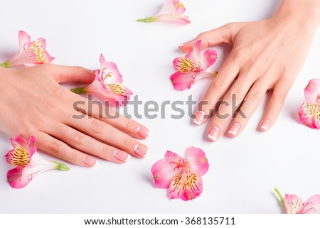 Beautiful female fingers with french manicure. Female hand with delicate flowers on a white background. - stock photo