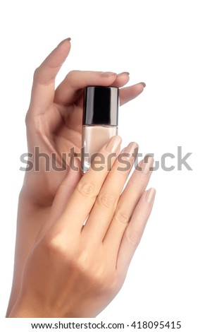 Beautiful female fingers with ideal naturel shiny beige manicure holding nail polish bottle. Care about female hands, healthy soft skin. Spa & cosmetics  - stock photo