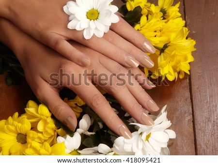 Beautiful female fingers with natural beige manicure touching spring flowers. Care about female hands, healthy soft skin. Spa & cosmetics. Close-up of beautiful fingers with nails polish  - stock photo