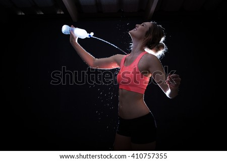 Beautiful female fitness model spraying herself with her waterbottle in a dark gym with a backlight effect to enhance the drops. - stock photo