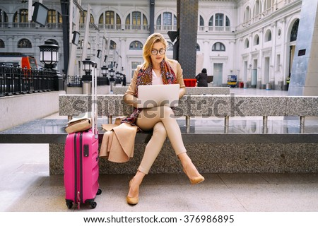 beautiful female freelancer using a laptop for distance work while waiting for the train.modern business woman checks e-mail on a laptop computer before the go on vacation - stock photo