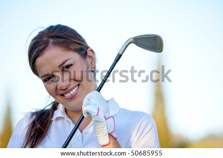 Beautiful female golf player at the course smiling - stock photo