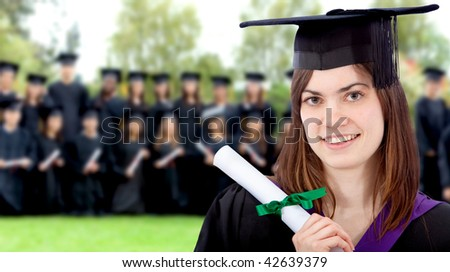 Beautiful female graduate outdoors with a group behind her - stock photo
