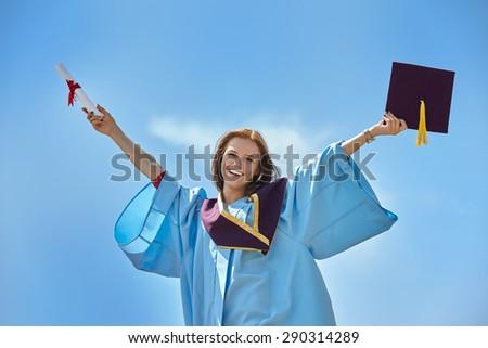 Beautiful female graduate wearing a graduation gown - stock photo