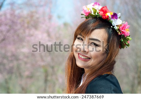 Beautiful female graduate wearing graduate grown and flower wreath - stock photo