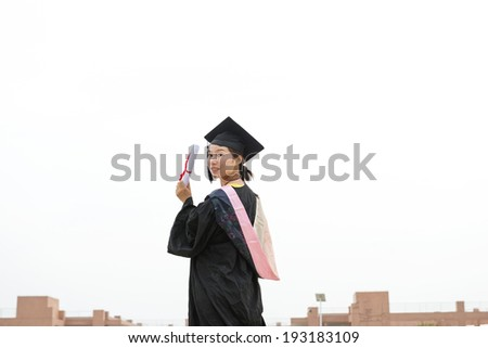Beautiful female graduate wearing graduation gown