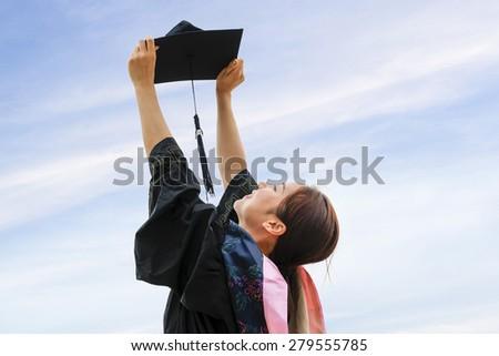 Beautiful female graduate wearing graduation gown - stock photo