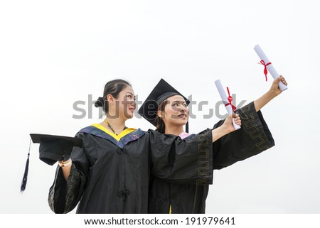 Beautiful female graduates wearing graduation gown