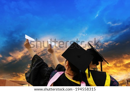 Beautiful female graduates wearing graduation gown, throwing airplane - stock photo