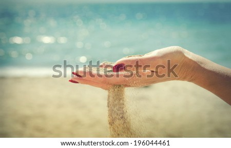 Beautiful female hand and the sand on the sea background - stock photo