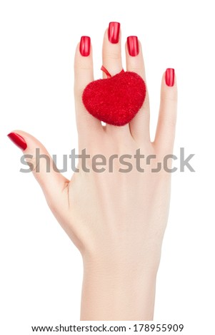 Beautiful female hand with a red heart on her finger.