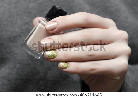 Beautiful female hand with warm beige nail design.