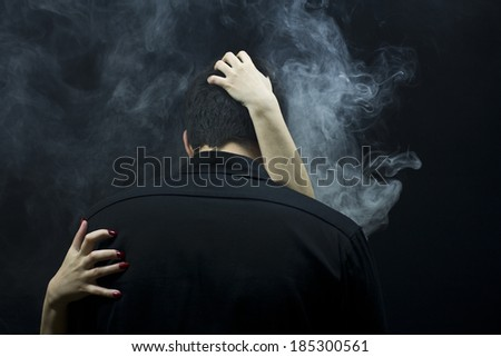 Beautiful female hands embrace high brunet. Black background. Smoke. - stock photo