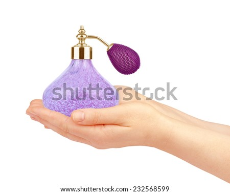 Beautiful female hands holding a bottle of perfume - stock photo