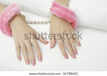 Beautiful female hands locked in the pink handcuffs on the sheets - stock photo