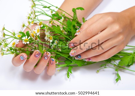 Beautiful female hands with art manicure holding a bouquet of chamomile on white background