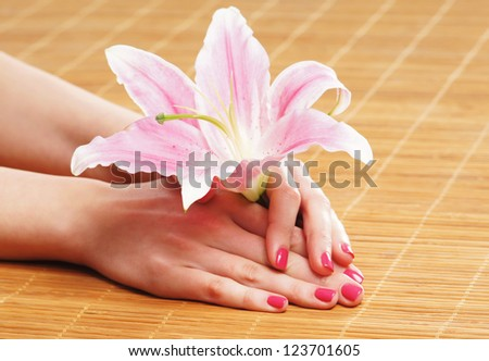 Beautiful female hands with flowers and petals in spa style