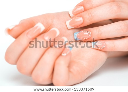 Beautiful female hands with french manicure on a light background with a shadow