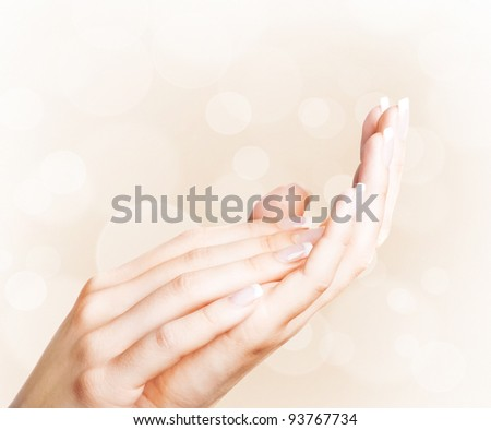 Beautiful female hands with french manicure with bokeh background - stock photo