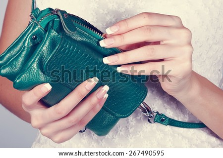 Beautiful female hands with manicure hold an open green handbag - stock photo