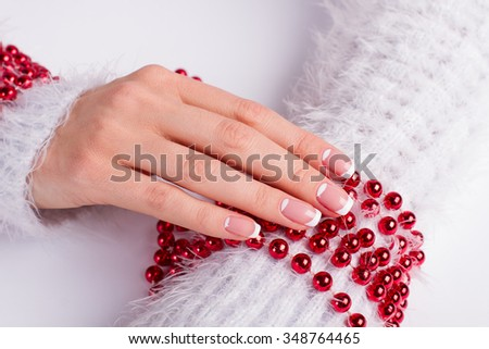 Beautiful female hands with New Year's manicure. French manicure on a background of red bracelet. - stock photo