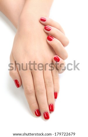 Beautiful female hands with red nail polish on the nails on a white background isolated