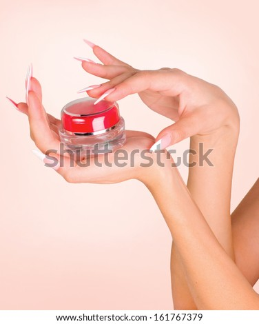 Beautiful female  hands with the cosmetic product  on a pink background  - stock photo