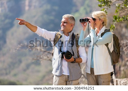 beautiful female hiker using binoculars while husband pointing  - stock photo