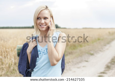 Beautiful female hiker using mobile phone on field - stock photo