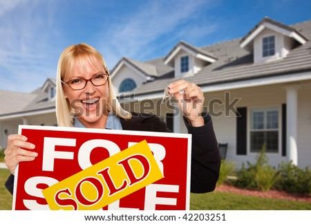 Beautiful Female Holding Keys to a New House & Sold Real Estate Sign. - stock photo
