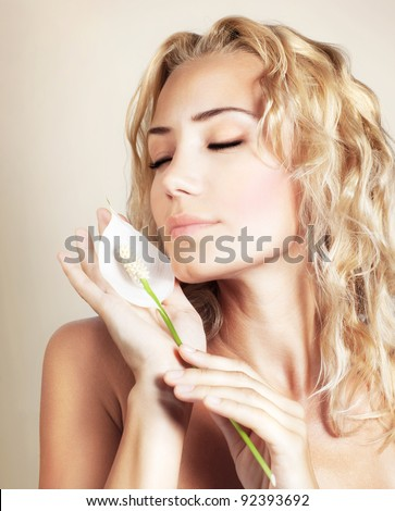 Beautiful female holding white calla flower, perfect clean skin, young girl portrait over beige background, beauty and spa concept - stock photo