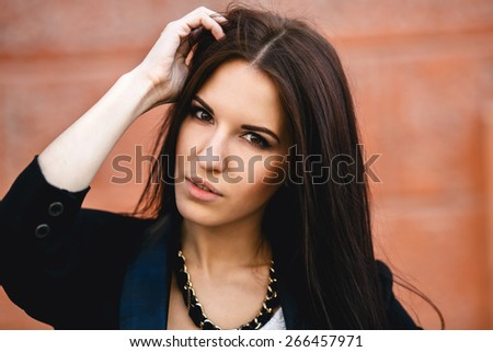 Beautiful female in a jacket on background of the wall