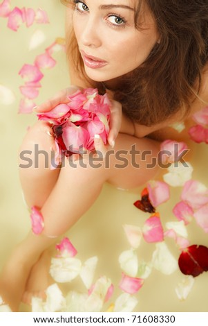 Beautiful female in bath with rose petal. Body care. - stock photo