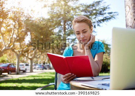 Beautiful female is reading diary while is relaxing in the fresh during her leisure in summer vacation, gorgeous woman is spending good time while she is sitting in park with book and laptop computer - stock photo