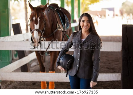 Beautiful female jockey carrying a helmet and posing next to her horse  - stock photo