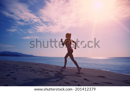 Beautiful female jogger with strong figure run on the sand along the sea ,silhouette of athletic girl on sea and sky background  - stock photo