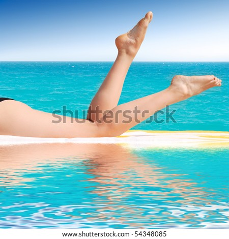 beautiful female legs between a pool and sea - stock photo